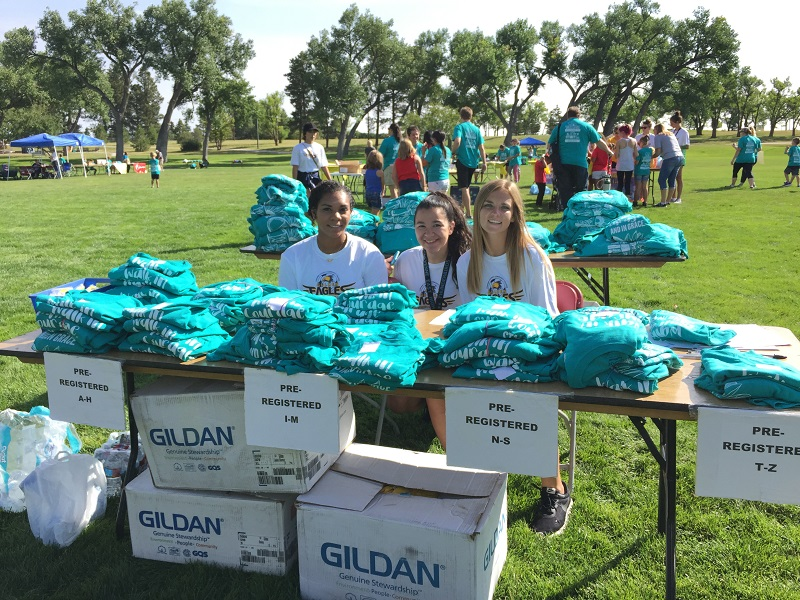 Grace for Two Brothers volunteers hand out T-shirts to entrants